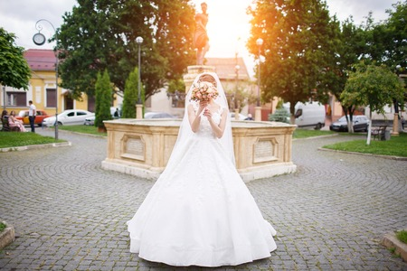 the bride in an elegant white dress stands near a monument in the city center