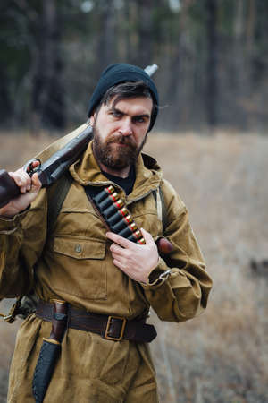 brutal bearded male hunter in a warm hat and khaki jacket with a rifle on his shoulder and ammunition on his chest on a background of green forest. Poacher with a weapon in his hands