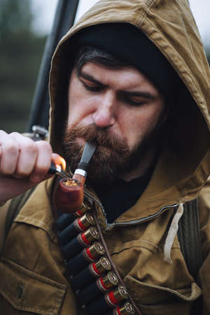 A bearded man-hunter in a black hat, in a hood, in a khaki jacket with a gun on his shoulder and cartridges on his chest smokes a pipe against the background of the forest