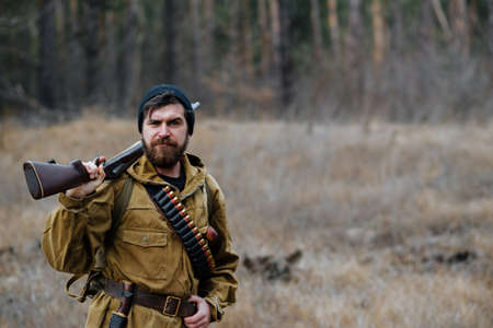 a bearded brutal hunter man in a dark warm hat, khaki jacket with a gun on his shoulder shaves his beard with a large sharp shiny knife against the background of the forest