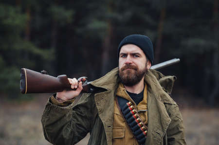 An experienced bearded male hunter in a warm hat and khaki jacket loads cartridges into a hunting rifle against the backdrop of a forest. Poacher seeks prey