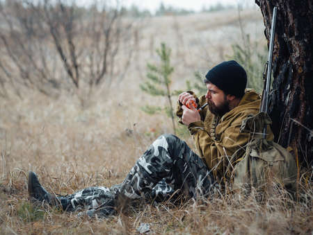 Bearded hunter with professional equipment walking in the woods