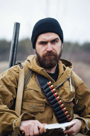An experienced male hunter with a beard in a green khaki jacket and a long cloak holds a gun in his hand directed towards the prey against the background of a dark forest