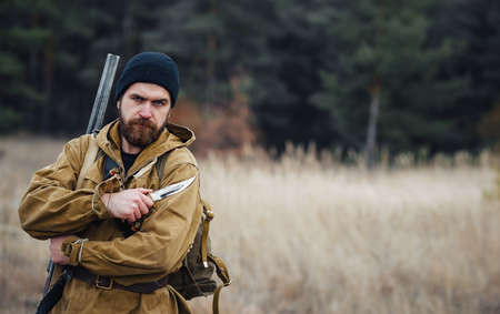 A serious man with a beard hunter in a dark hat and khaki jacket in a long cloak with a gun on his shoulder stands in a dark forest