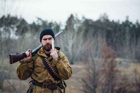 brutal bearded man hunter in a black hat and khaki jacket in a long cloak holds a gun in his hand directed towards the forest