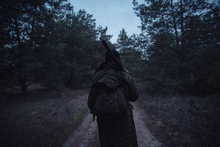 Stern man hunter with a beard in a hat and a green jacket, a coat with a rifle, ammunition and a backpack smokes a cigarette in a dark forest
