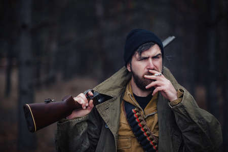 Serious brutal bearded man hunter in a dark hat and khaki jacket in a long cloak holds an unloaded gun against the background of a dark forest