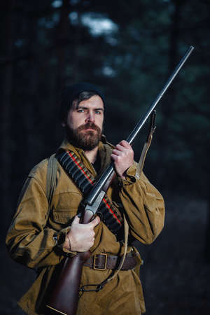 Old bearded man hunter in a warm hat, in a khaki jacket with a hunting rifle and a large backpack with cartridges against the background of a dark forest at night