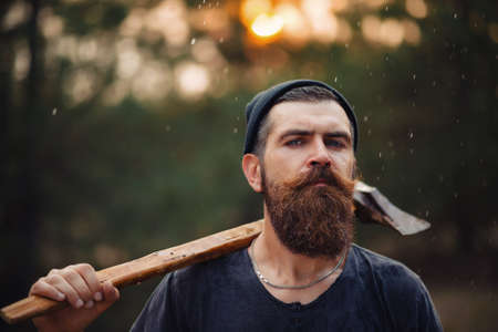 A serious man with a thick beard and a large mustache in a dark sleeveless T-shirt and a warm hat with gray hair holding a big ax against the background of a sunset forest under rain