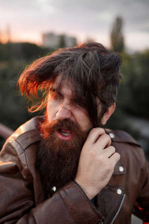 A grown male biker with a long beard, mustache and gray hair in a brown leather jacket leaned his face against an iron mesh fence at sunset. Banque d'images