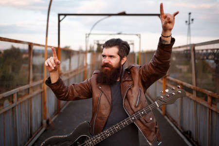Crazy bearded metalhead with big long mustache in brown leather jacket and jeans holds thumbs up and screams with black bass guitar on background of ground crosswalk