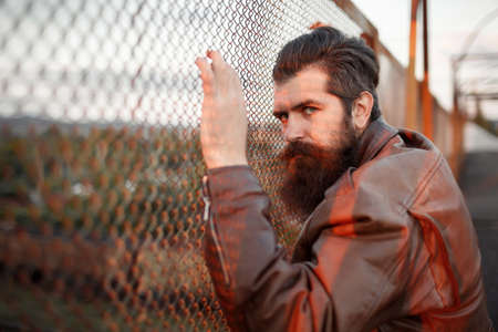 A grown male biker with a long beard, mustache and gray hair in a brown leather jacket leaned his face against an iron mesh fence at sunset. Police arrest