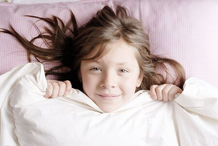 tender tenderness: little blond and smiling girl waking up on a sunny morning