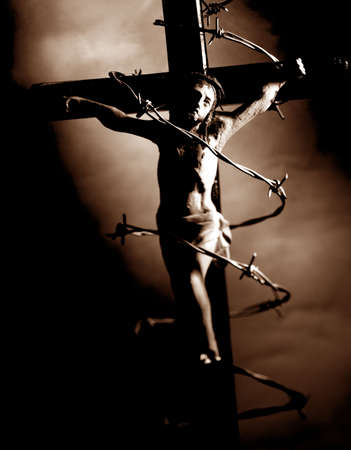 surrounded: figure of christ crucified in the cross illuminated with tenuous light surrounded with wire Stock Photo