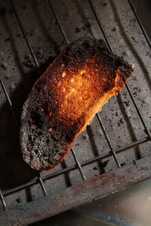 unsuitable: close up of burnt  bread on old black toasting