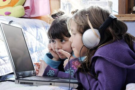 bussines people: two small girls, one with laptop and headphones pointing at the screen and the other watching it