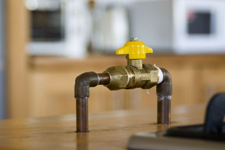 propane gas: Gas shut-off ball valve in a kitchen with blurry background