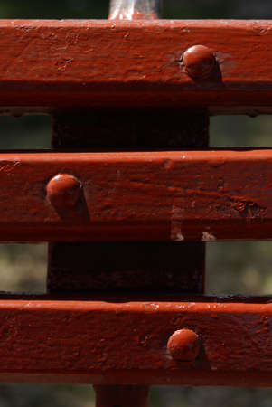 endorsement: close up and  detail of endorsement of wood seat painted of red color and three metallic rivets painted of red color  all illuminating of lateral form by the light of the sun