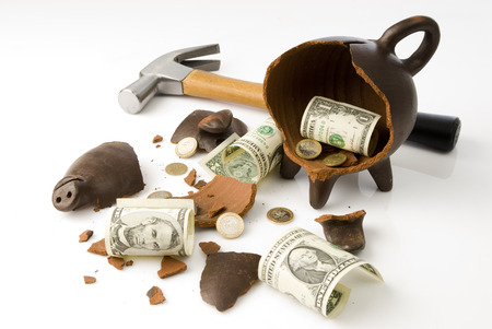 future earnings: a broken and empty clay piggy money box with money and hammer over white background