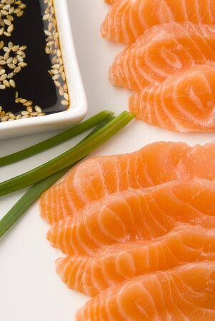 soja: raw salmon over white dish with soy sauce