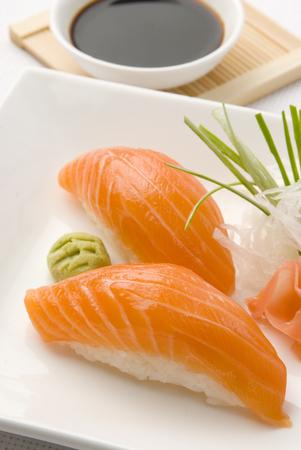 salmon sushi close up over white dish