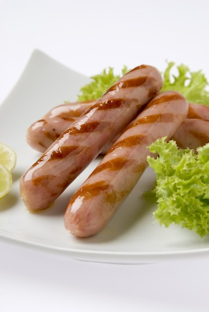 grilled sausages: close up of grilled sausages over white plate with blurry background