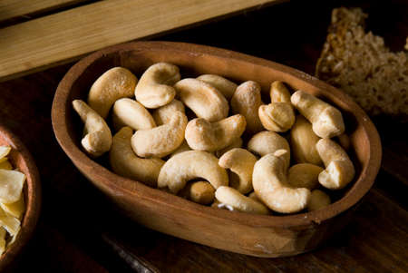 cashew nuts: some cashew nuts in a wood bowl, over dark background