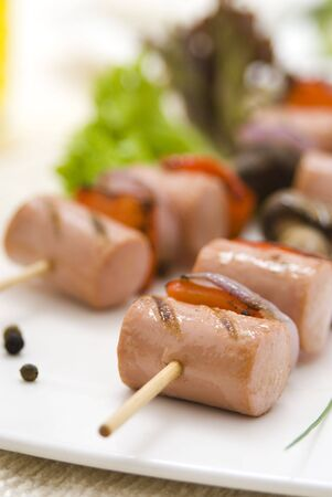 grilled sausages: close up of grilled sausages on wooden skewer over white plate with blurry background Stock Photo