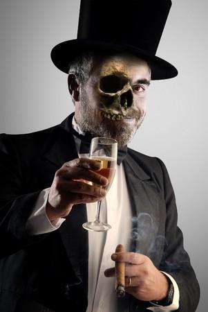 metáfora sobre el peligro del alcohol y el consumo de tabaco. Muestra un hombre bien vestido de fumar y beber con una calavera en lugar de su cara. aviso de esta manera el peligro.