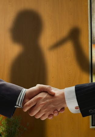 trickery: business handshake with shadows behind showing  real intentions, showing a man being stabbed in the back Stock Photo