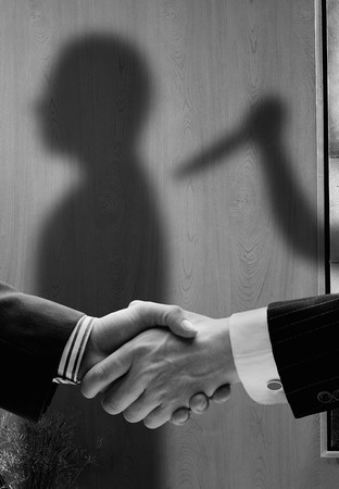 untruth: business handshake with shadows behind showing  real intentions showing a man being stabbed in the back