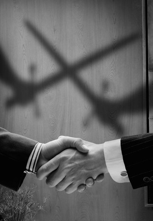 trickery: business handshake with shadows behind showing  real intention