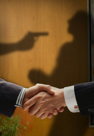 untruth: business handshake with shadows behind showing  real intention, with a man being shooted by the other