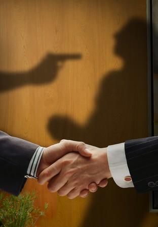 pacto: negocio apret�n de manos con sombras detr�s de la intenci�n real que muestra, con un hombre que se shooted por los dem�s