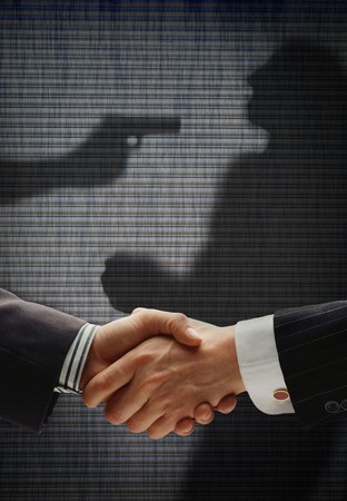 trickery: business handshake with shadows behind showing  real intention, with a man being shooted by the other