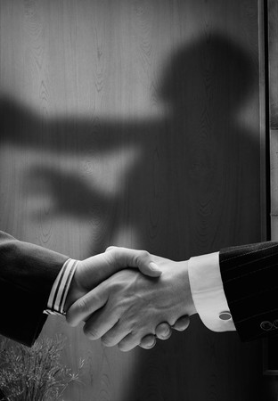 trickery: business handshake with shadows behind showing  real intentions, showing a man being hanged by the neck