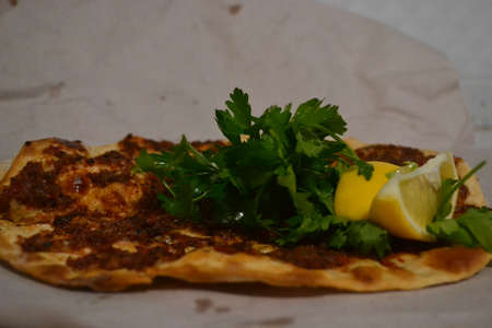 lahmacun is eaten with parsley and lemon