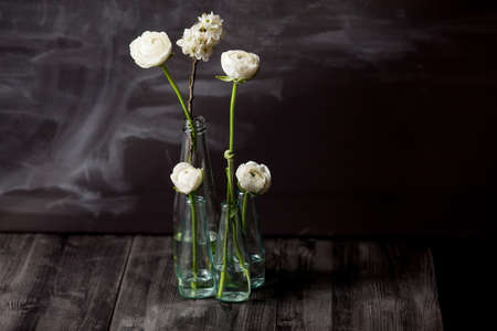 buttercups: Four white buttercups and blossom apple in small, glass bottles standing in the dark wooden floor with blackboard in the background