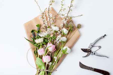 pruning scissors: Pink tulips, white anemones, white buttercups and blossom plum tree branch lying on wrapping paper from the top with knife and pruning scissors