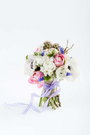 buttercups: Bouquet from pink tulips, violet grape hyacinths, white anemones, violet veronica and white buttercup with violet ribbon standing on white background Stock Photo