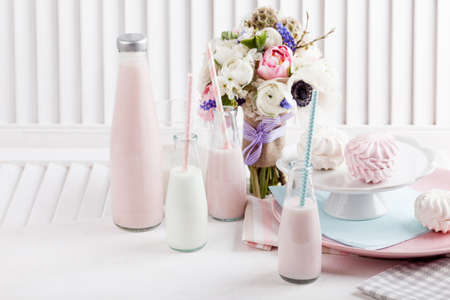 Four bottles of milkshakes, shutter with bouquet from pink tulips with violet ribbon Stock fotó