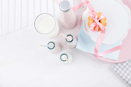 Four bottles of milkshakes, three with straws and glass of milk and plates with cookies tied with pink ribbon and cloth on white wooden shutter from the top Stock fotó - 56588178