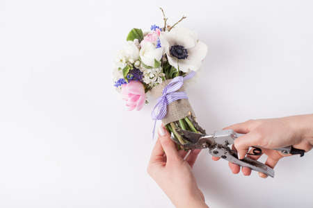 pruning scissors: Florist is prepering a bouquet from pink tulips, violet grape hyacinth with violet ribbon using pruning scissors Stock Photo