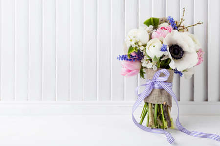 hyacinths: Bouquet from pink tulips, violet grape hyacinths with violet ribbon on white wooden shutter background Stock Photo