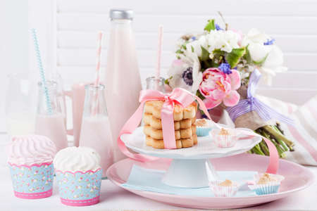 Four bottles of milkshakes, and plates with cookies, bouquet from pink tulips
