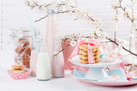 Four bottles of milkshakes, and glass of milk and plates with cookies and biscuits tied with pink ribbon, jar of candies Stock fotó