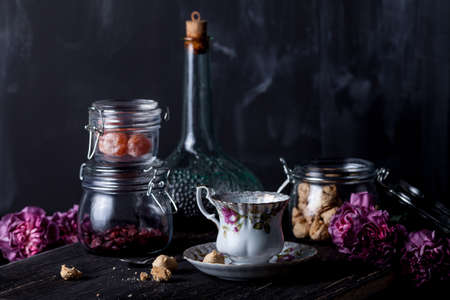 liqueur bottle: White, floral tea cup and jars with cookies, dryed cranberries, candied kumquat and bottle of liqueur and pink cloves on black, old wood on blackboard background Stock Photo