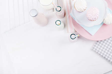 Four bottles of milkshakes, three with straws and glass of milk and plates with pink and white meringues and cloth on white wooden shutter from the top