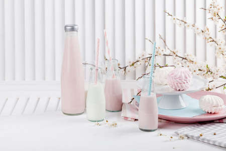 Four bottles of milkshakes, three with straws and plates with pink and white meringues and cloth on white wooden shutter with blossom apple tree in the background Stock fotó - 56633016