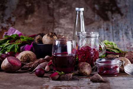Glass with fresh beetroots juice, with roots, beet leaves, cloth and jars in background with rusty metal Stock fotó